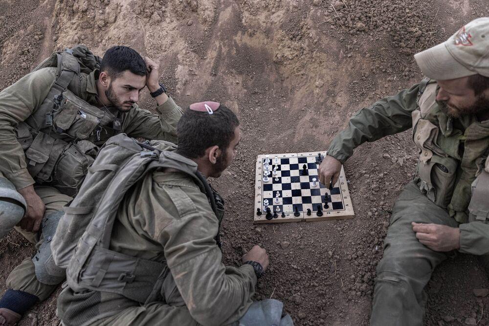 Soldados israelenses jogam xadrez em seu posto perto da fronteira entre Israel e Faixa da Gaza, 16 de agosto de 2021