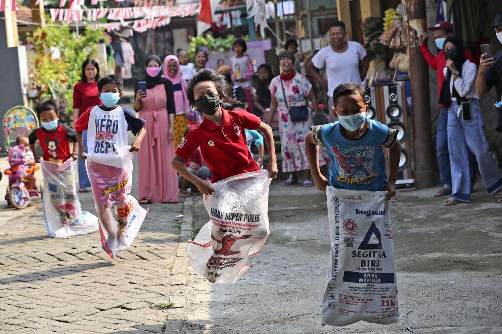 Crianças participam de corrida de sacos durante as comemorações do Dia da Independência em Jacarta, Indonésia, 17 de agosto de 2021