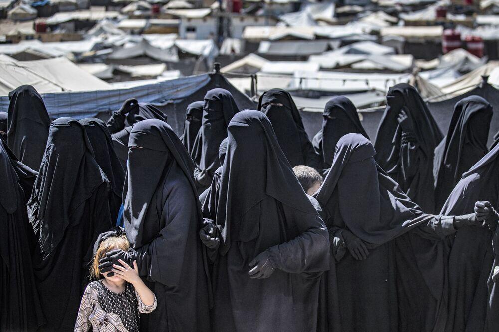 Mulheres e criança na fila para receber pacotes de ajuda humanitária no nordeste da Síria, 18 de agosto de 2021