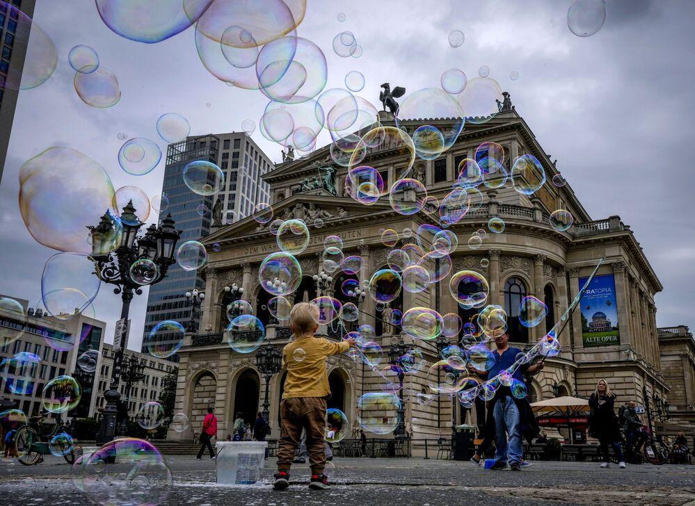 Menino brinca com bolhas de sabão em Frankfurt, Alemanha, 17 de agosto de 2021
