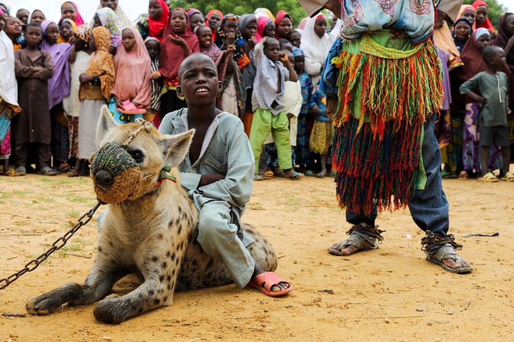 Menino sentado em hiena em uma atuação de circo na Nigéria, 27 de julho de 2021