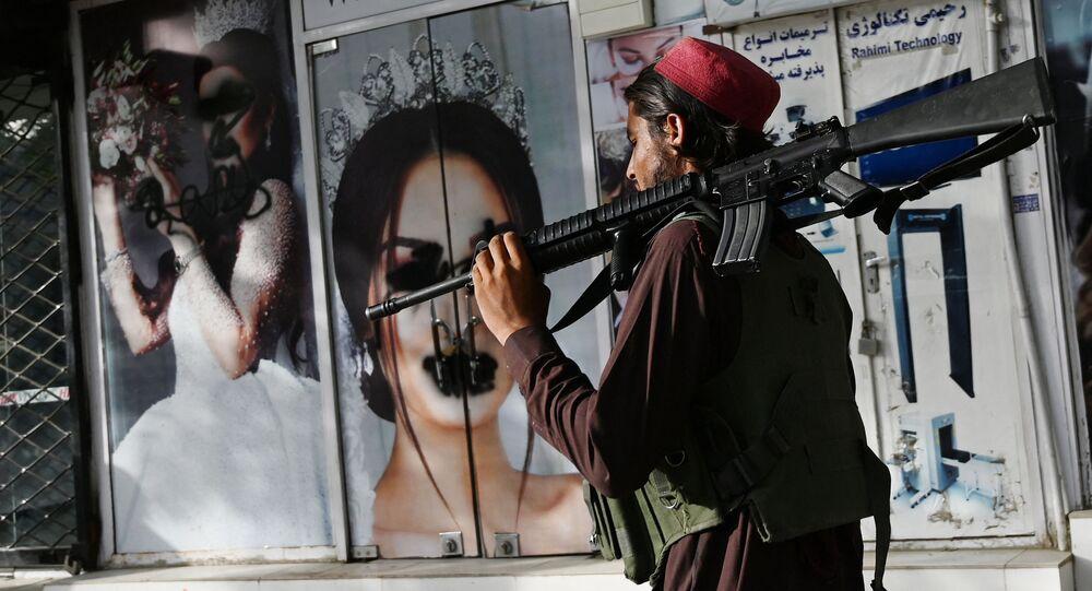 Militante do Talibã (organização terrorista proibida na Rússia e em vários outros países) passa por um salão de beleza com imagens de mulheres cobertas com tinta em Cabul, Afeganistão, 18 de agosto de 2021