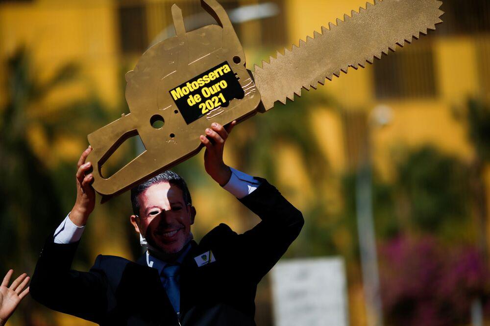 """Ativista de Greenpeace retratando Arthur Lira, presidente da Câmara, e segurando uma """"serra elétrica"""" em protesto contra a política ambiental do Congresso, 17 de agosto de 2021"""