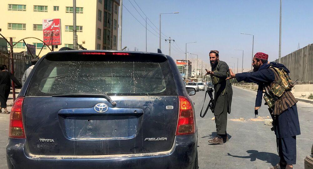 Membros do Talibã fazem gesto de controle de veículo em uma rua de Cabul, Afeganistão, 16 de agosto de 2021