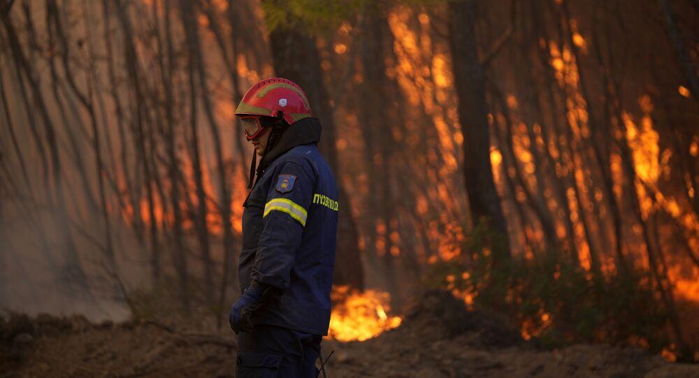 Bombeiro caminha por entre as chamas durante incêndio florestal na Grécia
