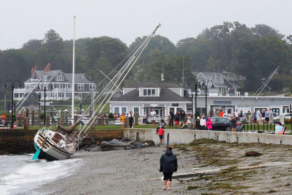 Pessoas olham para um veleiro após tempestade tropical Henri, em Jamestown, Rhode Island, EUA, 22 de agosto de 2021