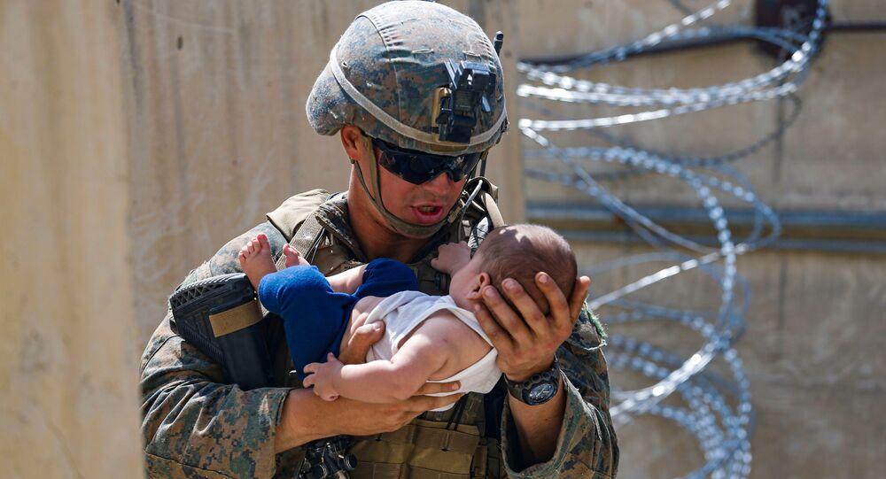Soldado dos EUA conforta um bebê durante evacuação no Aeroporto Internacional Hamid Karzai, Afeganistão, 21 de agosto de 2021