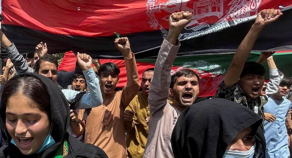Pessoas carregam bandeira nacional afegã durante protestos no Dia da Independência em Cabul, Afeganistão, 19 de agosto de 2021
