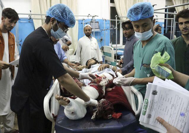 Pessoal médico e hospitalar carrega um homem ferido em maca para tratamento após explosões, Cabul, Afeganistão, 26 de agosto de 2021