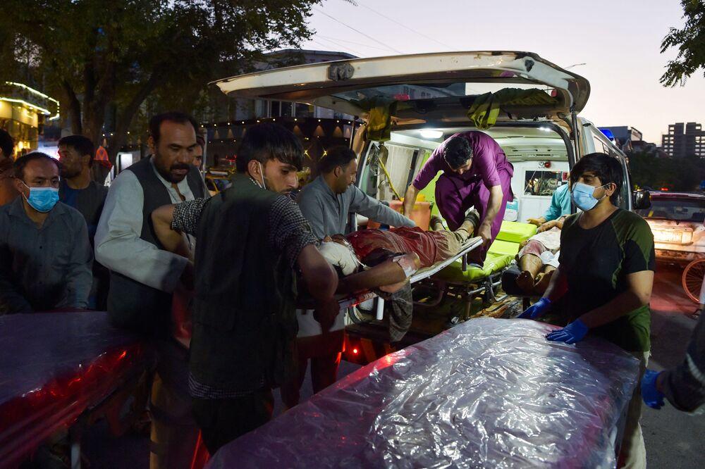 Voluntários e equipe médica trazem um homem ferido para tratamento, Cabul, Afeganistão, 26 de agosto de 2021