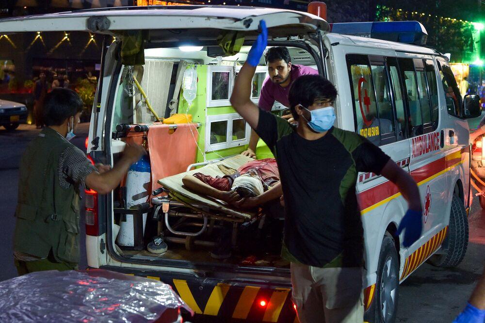 Equipe médica leva um homem ferido para um hospital em ambulância, Cabul, Afeganistão, 26 de agosto de 2021