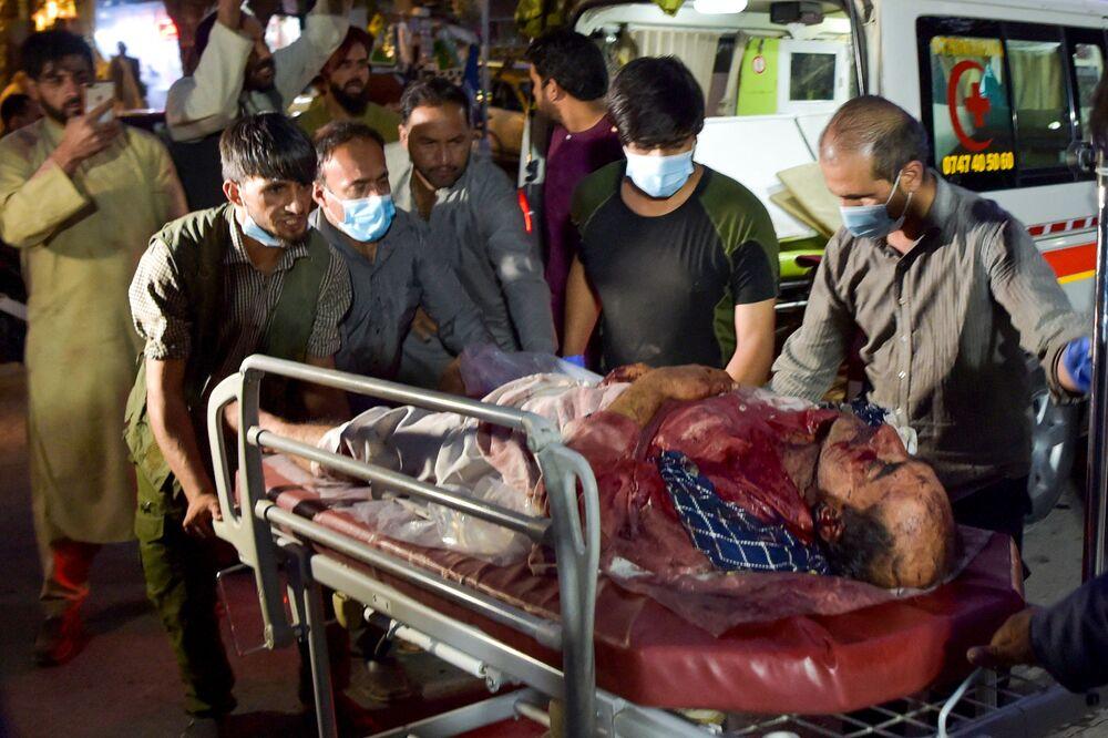 Equipe médica e voluntários levam um homem ferido para tratamento após fortes explosões em Cabul, Afeganistão, 26 de agosto de 2021