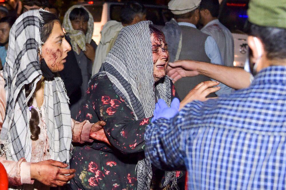 Mulheres feridas chegam a um hospital para tratamento após fortes explosões, Cabul, Afeganistão, 26 de agosto de 2021