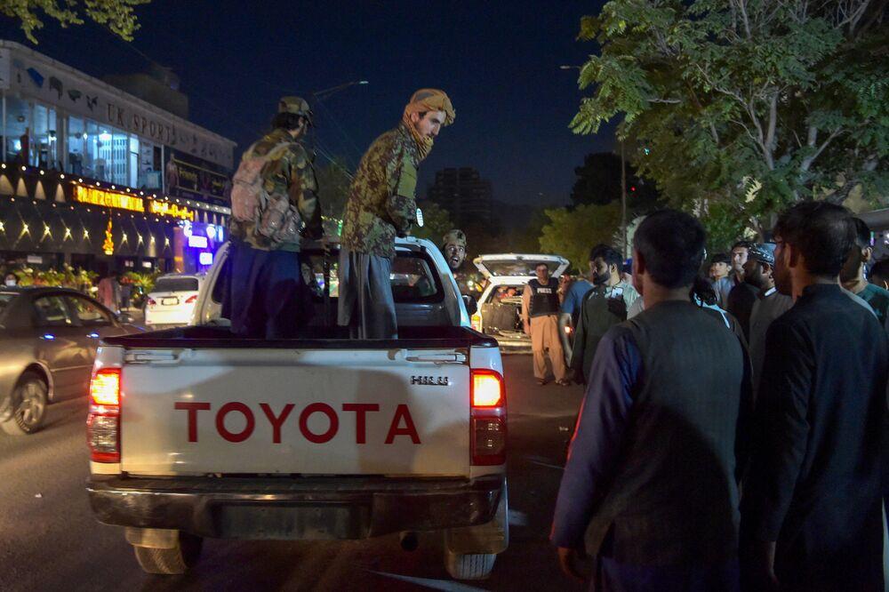 Militantes do Talibã (organização terrorista proibida na Rússia e em vários outros países) em uma caminhonete perto de um hospital, enquanto voluntários trazem feridos para tratamento, Cabul, Afeganistão, 26 de agosto de 2021