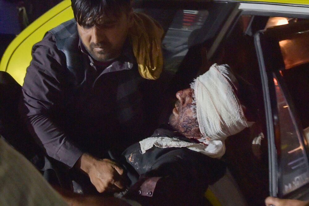 Homem retira um ferido de um carro para tratamento, Cabul, Afeganistão, 26 de agosto de 2021
