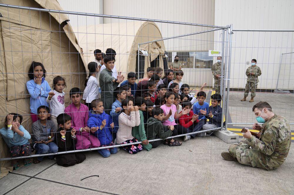 Soldado dos EUA toca guitarra para crianças afegãs recém-evacuadas na base aérea de Ramstein, Alemanha