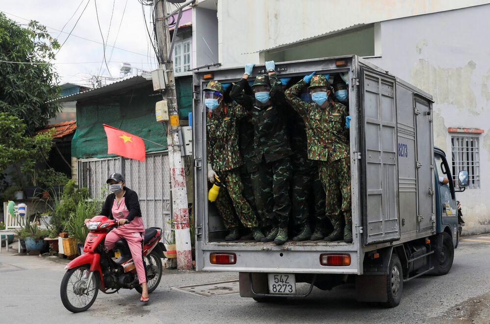 Soldados vietnamitas entregam alimentos na zona de isolamento rigoroso na cidade de Ho Chi Minh, Vietnã