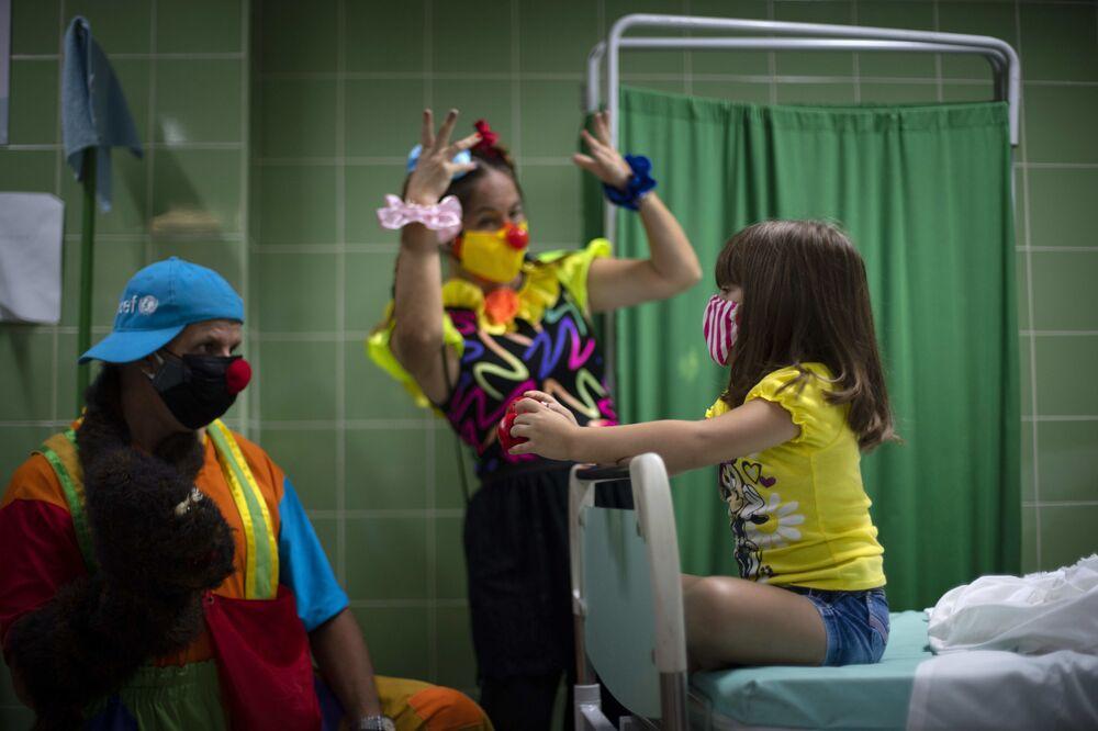 Palhaços entretêm uma garota vacinada em um hospital em Havana, Cuba