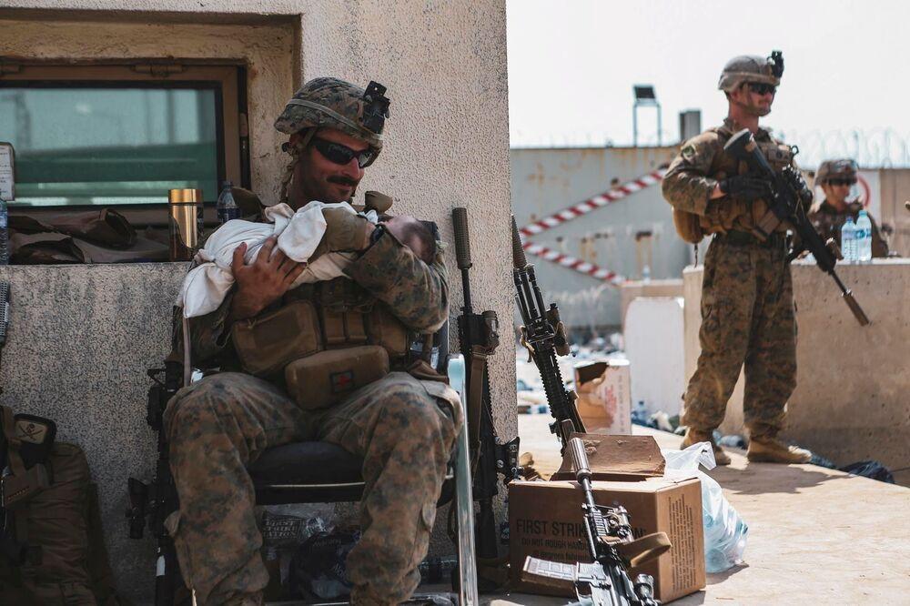 Fuzileiro naval dos EUA segura um bebê nos braços durante evacuação no Aeroporto Internacional de Cabul, Afeganistão