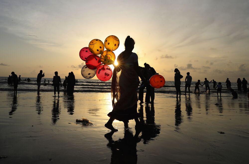 Mulher vende balões em uma praia de Mumbai, na Índia