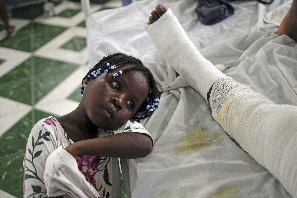 Moça acompanha no hospital sua mãe, que foi ferida no sequência do terremoto em Les Cayes, Haiti