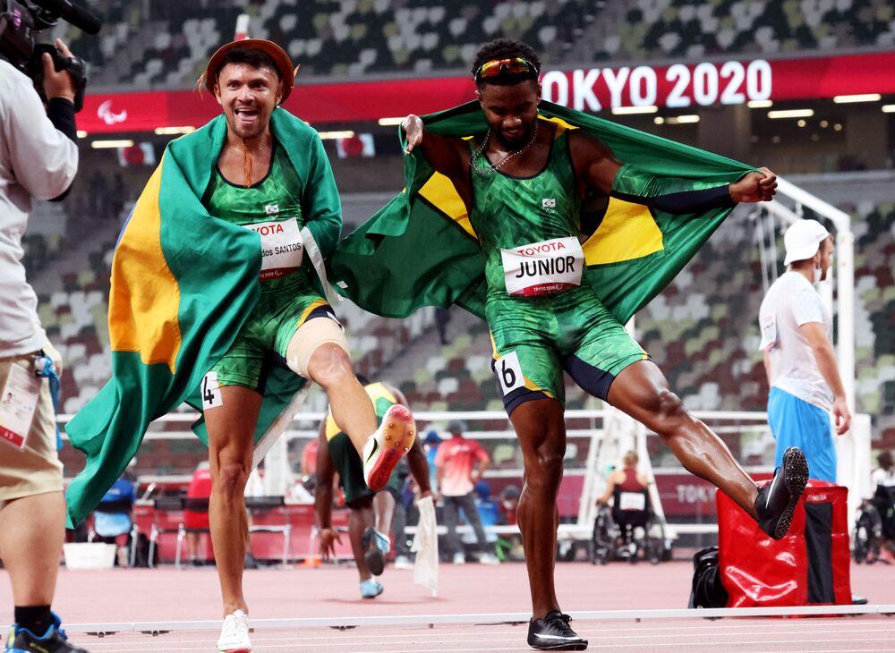 Medalhista paralímpico na prova de 100 m, na classe T47, Petrúcio Ferreira dos Santos, e medalhista de bronze Washington Junior comemoram com as bandeiras do Brasil após a competição