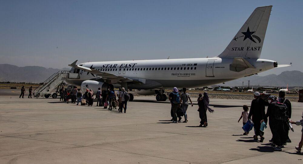 Evacuados são escoltados até uma aeronave durante uma evacuação no Aeroporto Internacional Hamid Karzai, Cabul, Afeganistão, 25 de agosto de 2021