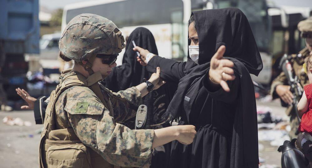 Fuzileiro naval dos EUA inspeciona mulher durante evacuação no Aeroporto Internacional Hamid Karzai, Cabul, Afeganistão, 28 de agosto de 2021