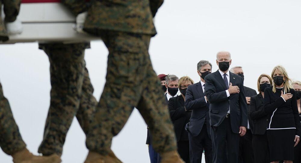 Presidente Joe Biden e primeira-dama Jill Biden olham para um caixão com os restos de um soldado americano transportado do Afeganistão, base aérea de Dover, EUA, 29 de agosto de 2021