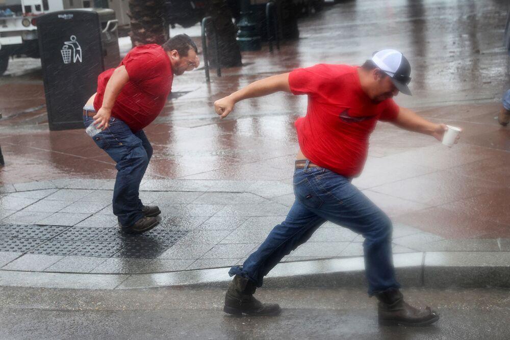 Pessoas lutam com o vento forte enquanto o furacão Ida atinge o estado da Louisiana, EUA, 29 de agosto de 2021