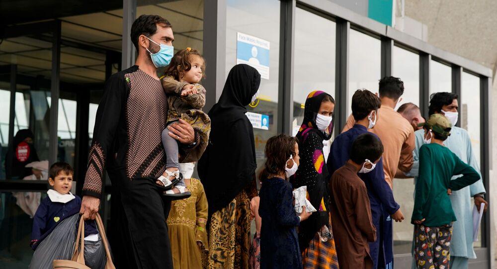 Refugiados afegãos caminham até um ônibus que os leva a um centro de processamento na chegada ao Aeroporto Internacional de Dulles em Dulles, Virgínia, EUA, 29 de agosto de 2021