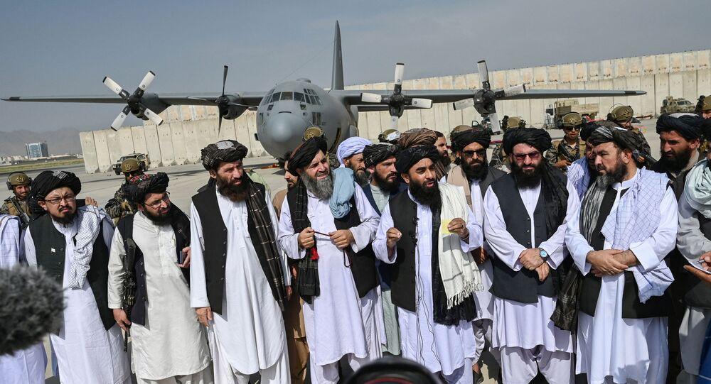 Porta-voz do Talibã, Zabihullah Mujahid (no centro com xaile), faz anúncio no aeroporto de Cabul após a saída das tropas americanas, 31 de agosto de 2021