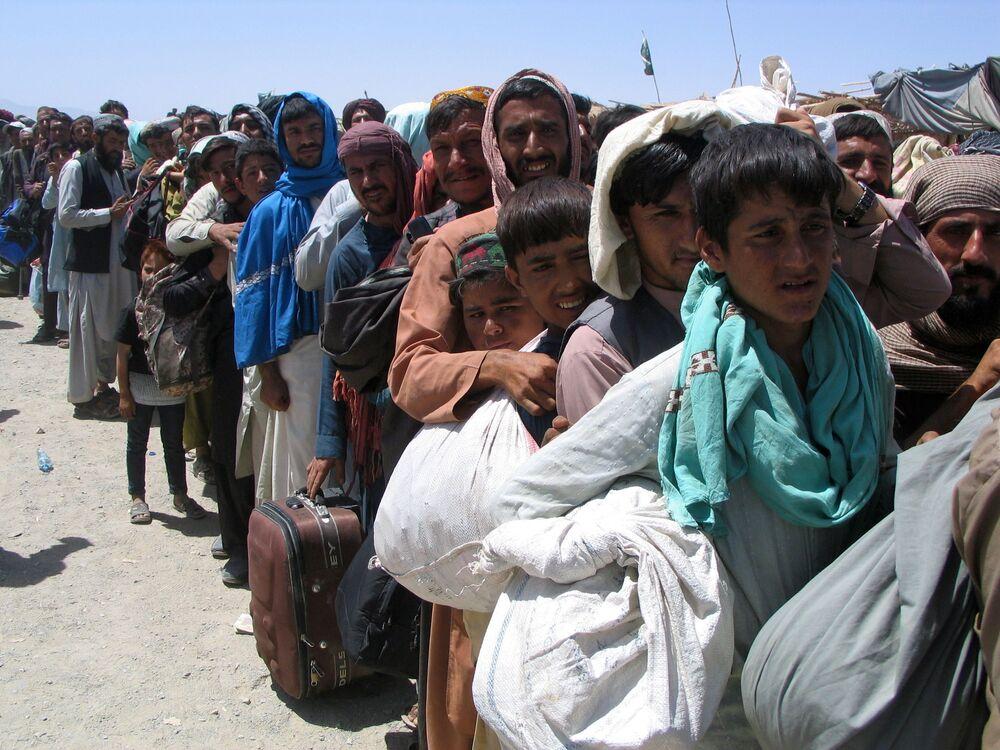 Pessoas aguardam na fila no Portão da Amizade para entrar no Afeganistão, na cidade fronteiriça de Chaman, Paquistão, 13 de agosto de 2021