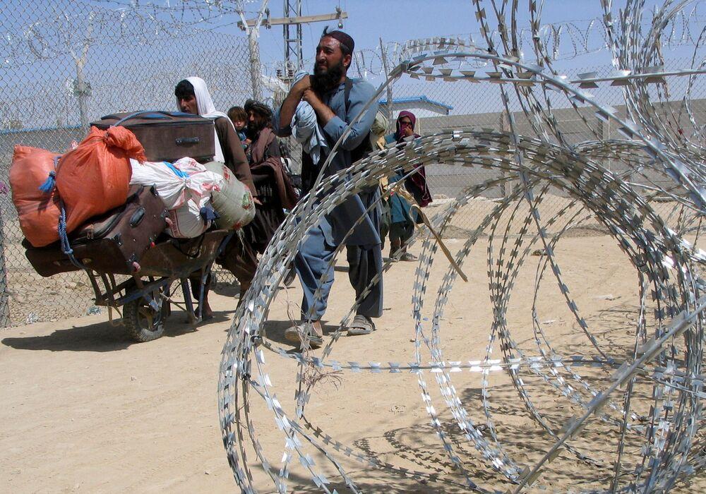 Uma família chegando do Afeganistão atravessa o Portão da Amizade, Paquistão, 19 de agosto de 2021
