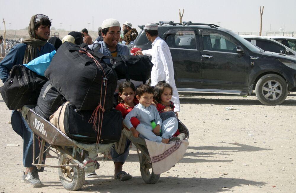 Uma família com seus pertences no Portão da Amizade, ponto de passagem na cidade fronteiriça de Chaman entre o Afeganistão e o Paquistão, 27 de agosto de 2021