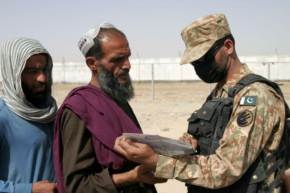 Soldado paquistanês verifica documentos das pessoas chegadas do Afeganistão, cidade fronteiriça de Chaman, Paquistão, 27 de agosto de 2021