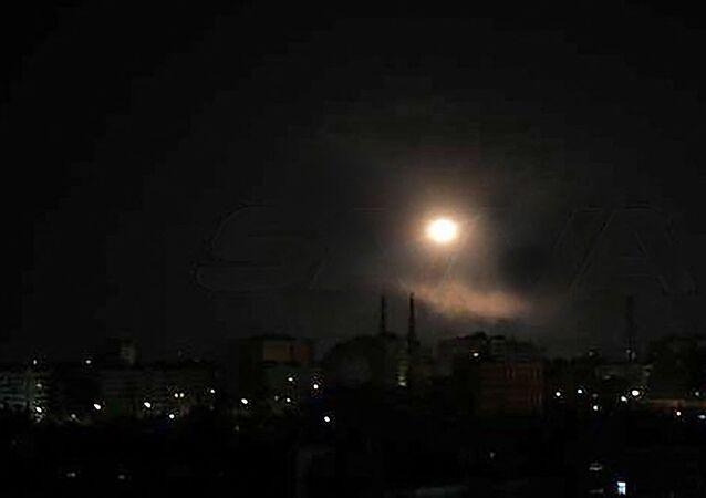 Imagem divulgada pela agência SANA em 20 de agosto de 2021 mostra um ponto de luz sobre a capital Damasco