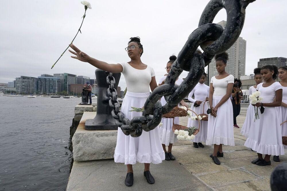 Membro da trupe Girlz of Imani do Centro de Artes Culturais OrigiNation joga cravos na baía de Boston durante a cerimônia de reconhecimento da escravidão em Boston