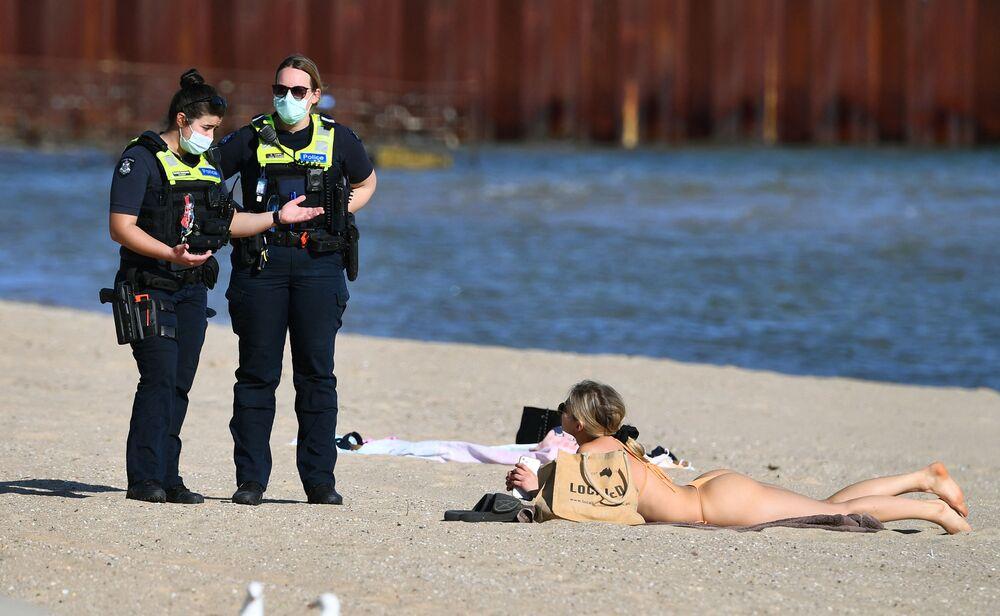 Policiais falam com mulher tomando banhos de sol na praia de St. Kilda, em Melbourne durante o regime de quarentena na Austrália