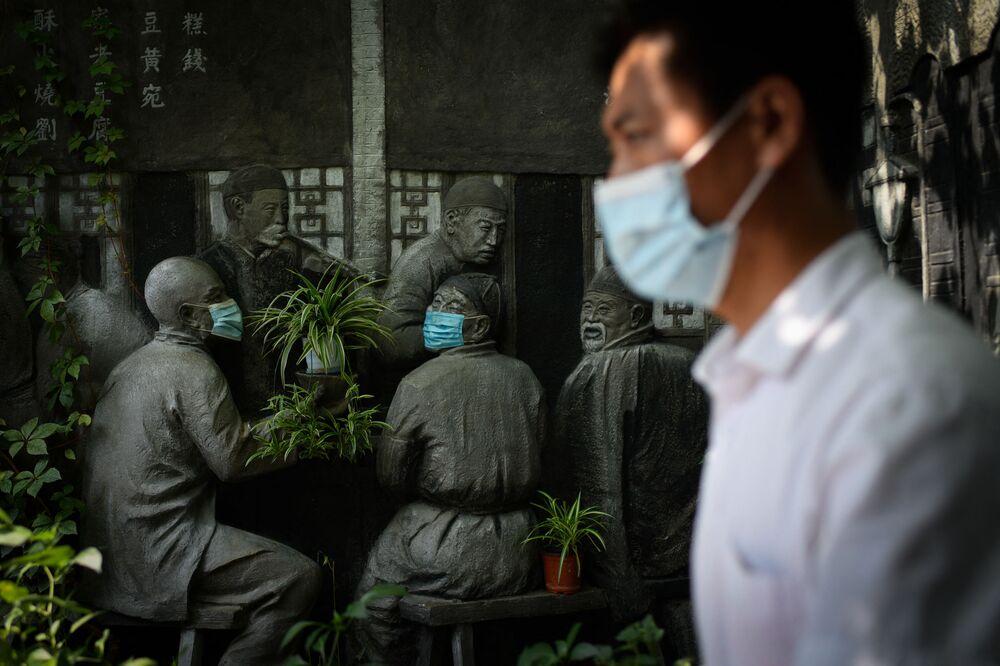 Homem passa por escultura com máscaras perto de um restaurante em Pequim, China