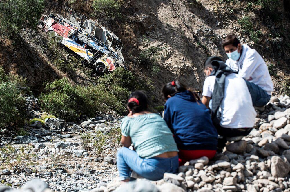 Pessoas sentadas perto do local de acidente de ônibus no Peru