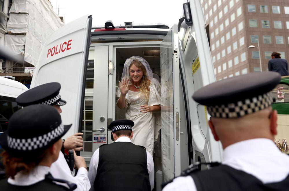 Ativista em vestido de noiva em carro da polícia durante o protesto da Extinction Rebellion em Londres, Reino Unido