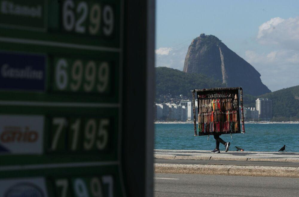 Vendedor de rua caminha ao longo da praia de Copacabana, 2 de setembro de 2021