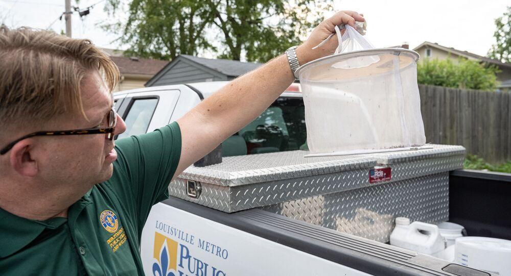 Matthew Vanderpool, especialista em saúde ambiental, segura uma armadilha de mosquitos em 25 de agosto de 2021 em Louisville, Kentucky, EUA