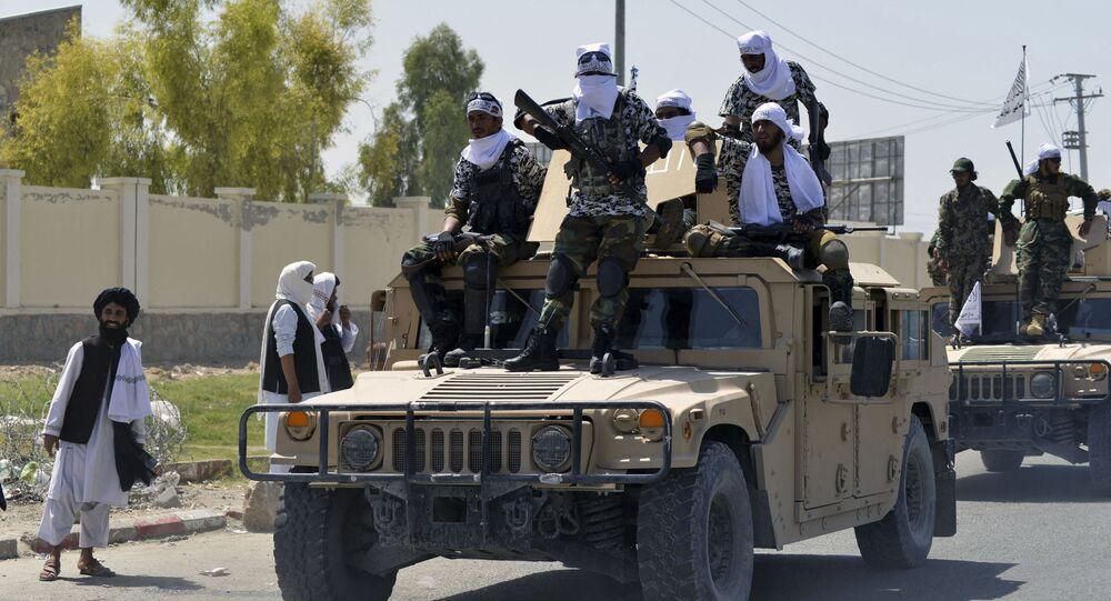 Combatentes talibãs em veículos militares Humvee desfilando ao longo de uma rodovia para comemorar a retirada das forças dos EUA do Afeganistão, em Kandahar