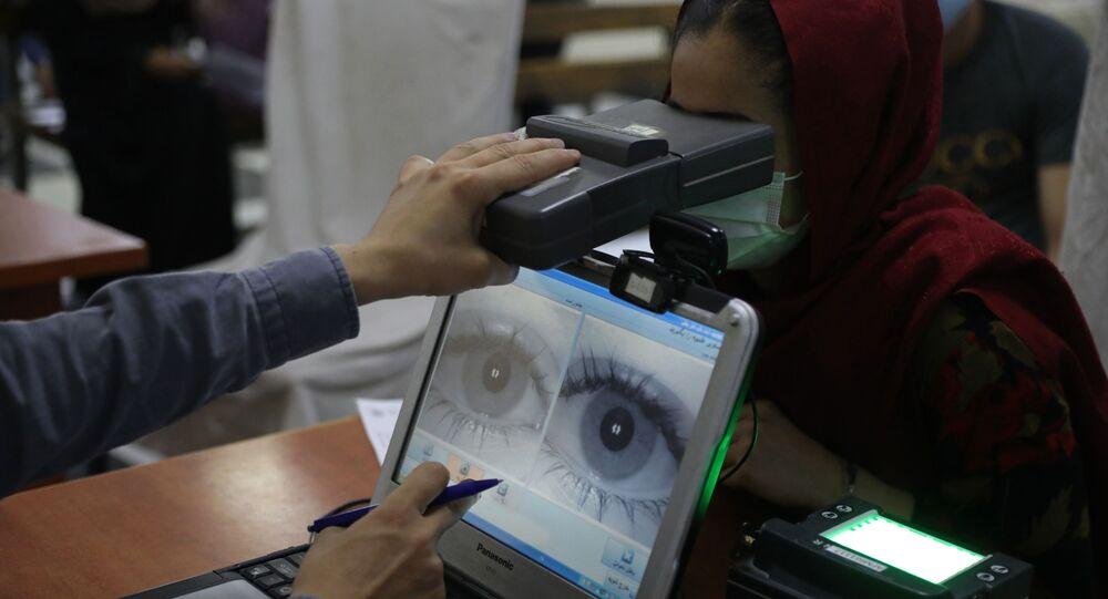 Um funcionário examina os olhos de uma mulher em busca de dados biométricos necessários para solicitar um passaporte, no escritório de passaportes em Cabul, Afeganistão, 30 de junho de 2021