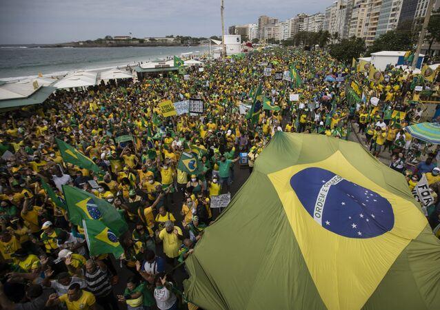 Apoiadores do presidente Jair Bolsonaro (sem partido) carregam a bandeira do Brasil na praia de Copacabana, no Rio de Janeiro, em 7 de setembro de 2021