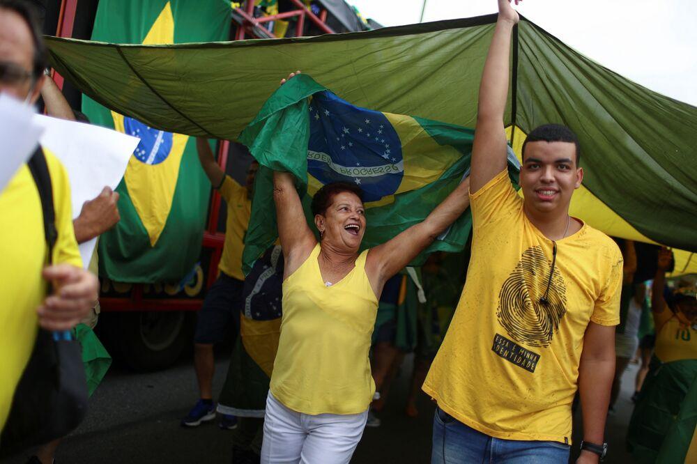 Pessoas participantes da marcha pelo Dia da Independência seguram bandeira do Brasil, em 7 de setembro de 2021