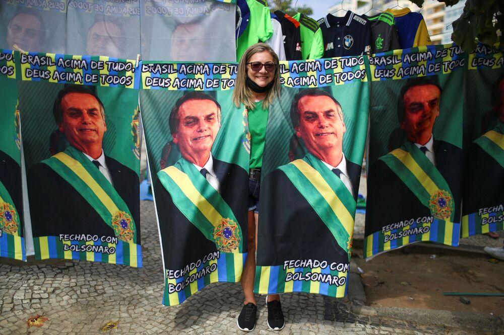Mulher apoiadora de Bolsonaro posa para foto no meio de cartazes com retrato do presidente brasileiro, em 7 de setembro de 2021