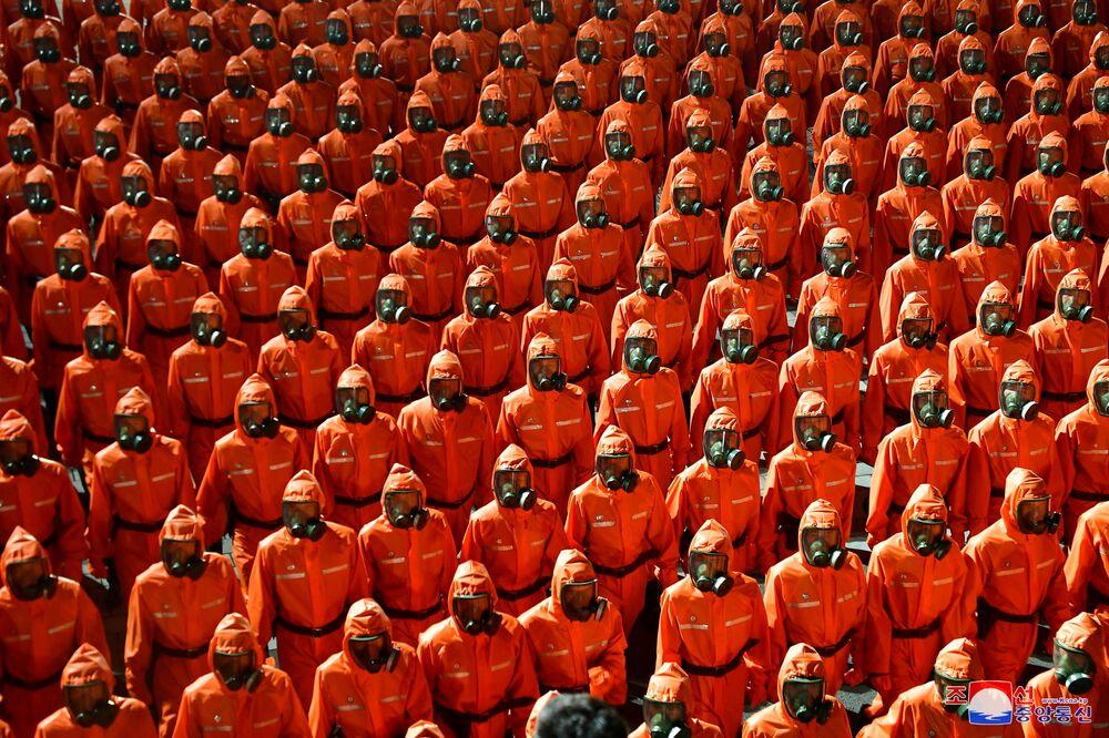 Pessoas marchando com trajes de proteção biológica durante a parada militar no 73º aniversário da fundação da Coreia do Norte, 9 de setembro de 2021